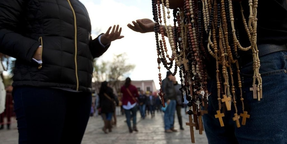 FILE - In this Feb. 14, 2016 file photo, a woman buys a rosary from a street vendor, in San Cristobal de las Casas, Mexico. On Monday, Pope Francis will travel to the southern indigenous state of Chiapas, Mexico's poorest and least Catholic region. A new study released by the National Statistics Institute Tuesday, Dec. 13, 2016, finds that about 58 percent of jobs in Mexico are in the informal sector, which includes categories such as unregistered vendors, artisans and domestic workers. (AP Photo/Moises Castillo, File)