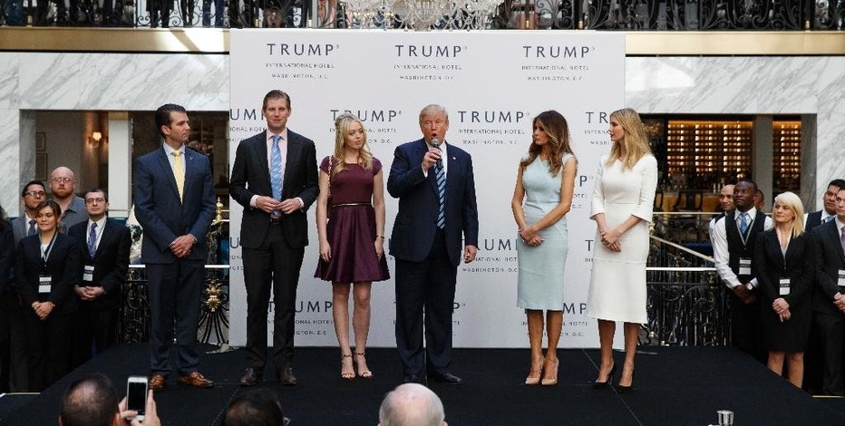 FILE - In this Oct. 26, 2016, file photo, Republican presidential candidate Donald Trump, accompanied by, from left, Donald Trump Jr., Eric Trump, Trump, Melania Trump, Tiffany Trump and Ivanka Trump, speaks during the grand opening of the Trump International Hotel- Old Post Office, in Washington. Trump had planned a news conference for Thursday on the future of his business but announced Monday, Dec. 12, he would postpone it until next month. (AP Photo/ Evan Vucci, File)