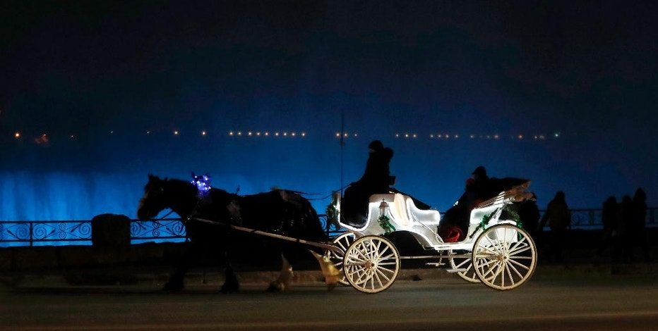 In this Saturday, Dec. 10, 2016 photo, people ride in a horse-drawn carriage in front of the Niagara Falls illuminated by new LED lights, in Niagara, Ontario. The natural wonder is shining more brightly than ever before on these dark winter nights: New high-tech LED lights are illuminating Niagara Falls. (AP Photo/Julio Cortez)