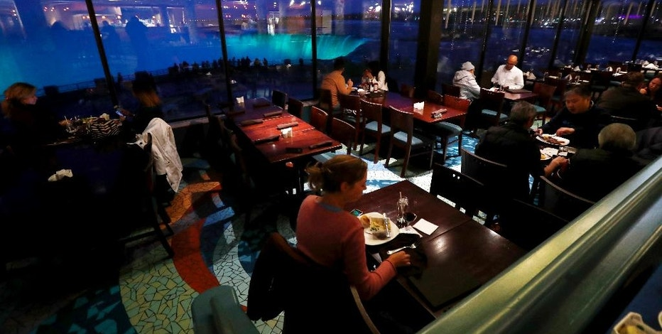 In this Saturday, Dec. 10, 2016 photo, people dine at the Elements Cafe overlooking the Niagara Falls illuminated by new LED lights, in Niagara, Ontario. Visitors unwilling to brave the frigid air outdoors can watch Niagara Falls illuminated after dark from the windows of hotels and restaurants on the Canadian shore. (AP Photo/Julio Cortez)