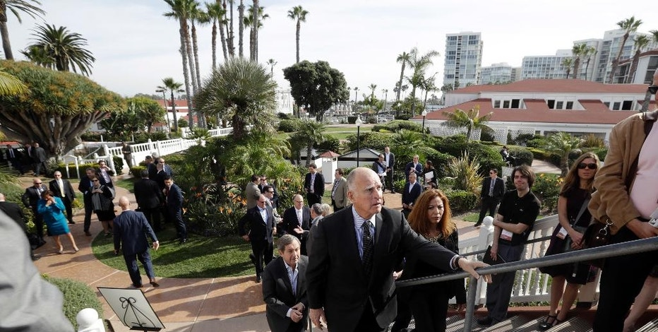 California Gov. Jerry Brown, center, arrives for a news conference ahead of Canadian Ambassador David MacNaughton, behind, during the Western Governors Association winter meeting at the Hotel del Coronado Tuesday, Dec. 13, 2016, in Coronado, Calif. Brown announced Tuesday a proposal to permanently ban new offshore oil and gas drilling in the state, during an event to launch a new organization aimed at protecting oceans, called the International Alliance to Combat Ocean Acidification. (AP Photo/Gregory Bull)