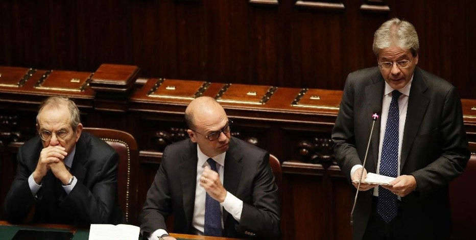 Italian Prime Minister Paolo Gentiloni, right, gives his first speech as premier at the lower house where he will later face a confidence vote, in Rome Tuesday, Dec. 13, 2016. Paolo Gentiloni, a Democrat formerly serving as foreign minister, formed Italy's new government Monday, keeping several key ministers from the coalition of Matteo Renzi, who resigned last week. At left is Finance minister Pier Carlo Padoan, at center is Foreign minister Angelino Alfano. (AP Photo/Alessandra Tarantino)