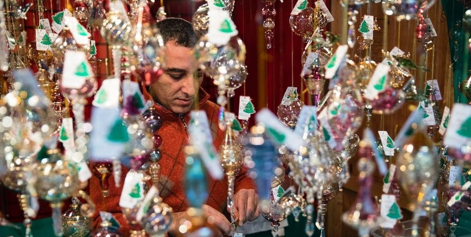 In this Thursday, Dec. 8, 2016, photo, Hani Mikhail places a label on one of his mouth-blown glass ornaments for sale at his booth set up for the holidays at City Hall in Philadelphia. On Wednesday, Dec. 14, 2016, the Commerce Department releases U.S. retail sales data for November. (AP Photo/Matt Rourke)