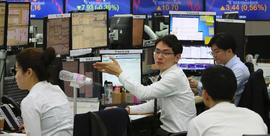 Currency traders work at the foreign exchange dealing room of the KEB Hana Bank headquarters in Seoul, South Korea, Thursday, Dec. 15, 2016. Share benchmarks in Asia are seeing moderate losses early Thursday, after the Federal Reserve raised interest rates overnight. The quarter percentage point rate increase, the second in a decade, was widely expected although investors were surprised to see the Fed project three more increases for 2017. (AP Photo/Ahn Young-joon)