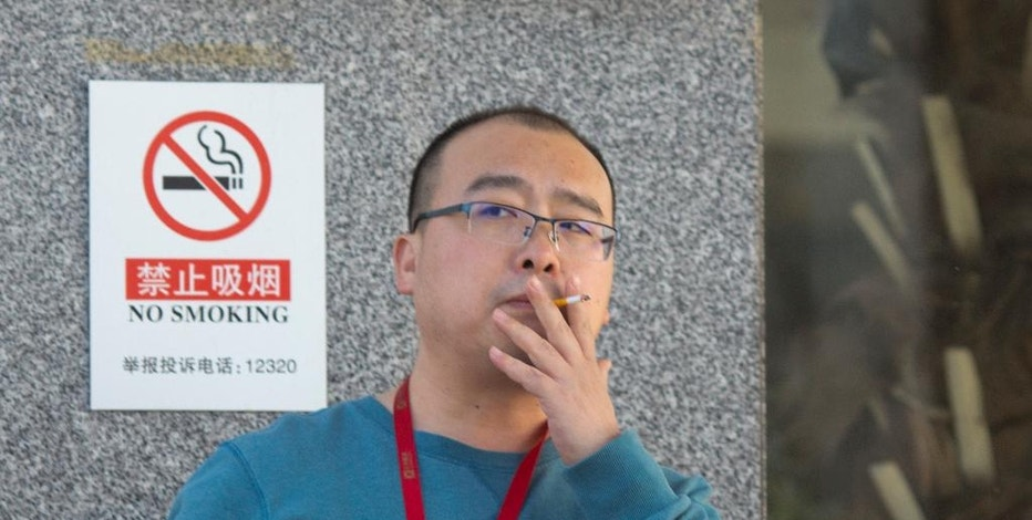 In this Friday, Dec. 2, 2016 photo, a man smokes near a no-smoking sign outside an office building in Beijing. As China considers a nationwide ban on smoking indoors, the fight is well underway in Beijing, which banned smoking in restaurants and other public places 18 months ago. Zealous volunteers and anti-smoking advocates have made some headway against millions of occasionally intransigent smokers and the state-run cigarette monopoly, a large and powerful force in China's government and economy. (AP Photo/Ng Han Guan)