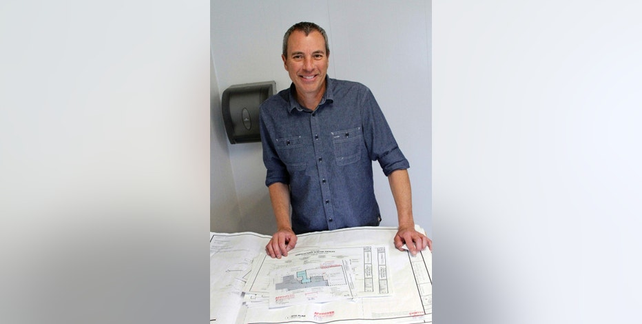 FILE - In this Oct. 5, 2016 file photo, Bryant Thorp poses with plans for his marijuana retail store, Arctic Herbery, in Anchorage, Alaska. The first retail marijuana store in Alaska's largest city is set to open Thursday, Dec. 15, 2016, and so many people are expected at the small store that shuttle buses will ferry customers in. Owner Bryant Thorp has set the opening for high noon at Arctic Herbery, a small nondescript shop in a busy industrial and residential area of midtown Anchorage. (AP Photo/Mark Thiessen, File)