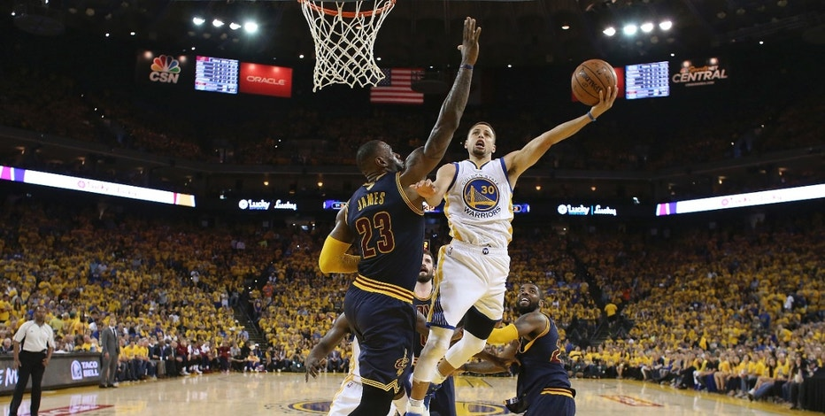 Golden State Warriors guard Stephen Curry (30) shoots against Cleveland Cavaliers forward LeBron James (23) during the first half of Game 2 of basketball's NBA Finals in Oakland, Calif., Sunday, June 5, 2016.