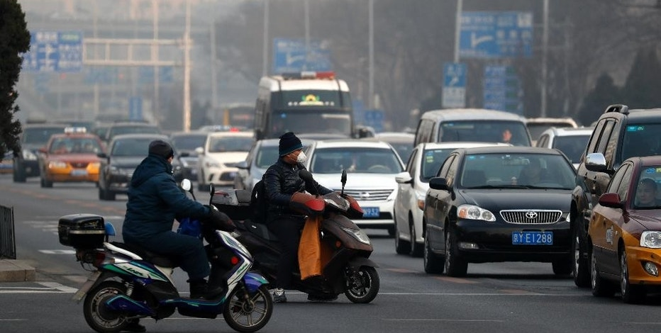 Electric bike riders wearing mask to protect themselves from exhaust gas wait at a traffic lights junction during a heavily polluted day in Beijing, Sunday, Dec. 18, 2016. China's capital and other northern cities have banned half of all vehicles from city streets and ordered factories, schools and construction sites closed in response to a five-day smog red alert. (AP Photo/Andy Wong)