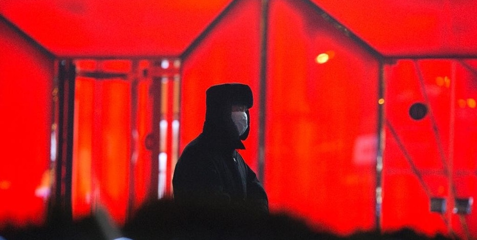 A security guard wears a mask during duty in Beijing, China, Saturday, Dec. 17, 2016. China's capital and other northern cities have banned half of all vehicles from city streets and ordered factories, schools and construction sites closed in response to a five-day smog red alert. (AP Photo/Ng Han Guan)