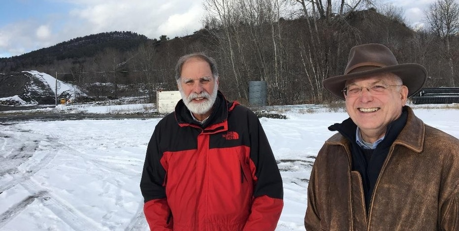 "In this Dec. 8, 2016 photo, Steve Burke and Jim Besha of Albany Engineering Corp. stand at the site of an abandoned iron mine in the Adirondacks, in Mineville, N.Y., where they're seeking a federal permit to build an underground hydroelectric pumped storage project. The hills behind them are ""tailings"" leftover from crushing ore to extract iron from the mine that closed in 1971. (AP Photo/Mary Esch)"