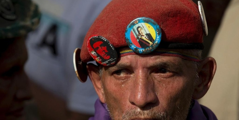 "A man wears a red beret with the image of late Venezuela's President Hugo Chavez and of Cuba's revolutionary hero Ernesto ""Che"" Guevara during a rally in Caracas, Venezuela, Saturday, Dec. 17, 2016. Venezuela's President Nicolas Maduro called for a pro-government rally as the country to give a tribute to the Venezuelan hero Simon Bolivar meanwhile the country is on edge over his so-far failed plan to introduce larger-denominated bills to fight soaring inflation. (AP Photo/Fernando Llano)"