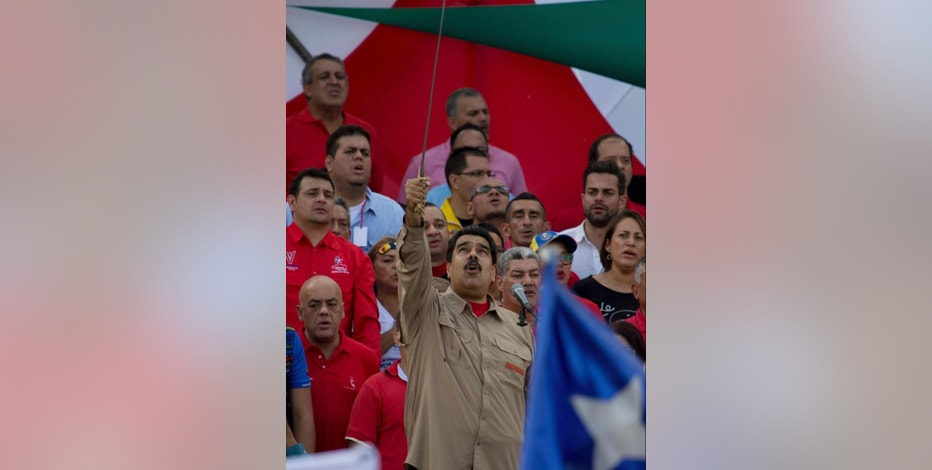 Venezuela's President Nicolas Maduro, holds up a sword of Venezuelan hero Simon Bolivar as he sings the national anthem during a rally in Caracas, Venezuela, Saturday, Dec. 17, 2016. Maduro called for a pro-government rally as the country to give a tribute to the Venezuelan hero Simon Bolivar meanwhile the country is on edge over his so-far failed plan to introduce larger-denominated bills to fight soaring inflation.(AP Photo/Fernando Llano)