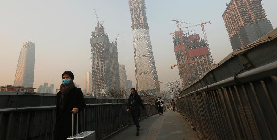 "People, some wearing masks for protection against air pollution, walk on a pedestrian overhead bridge in Beijing as the capital of China is shrouded by heavy smog Monday, Dec. 19, 2016. Engulfed in choking smog, some northern Chinese cities limited the number of cars on roads and temporarily shut down factories on Monday to cut down pollution during a national ""red alert."" More than 700 companies stopped production in Beijing and traffic police were restricting drivers by monitoring their license plate numbers, state media reported. (AP Photo/Andy Wong)"