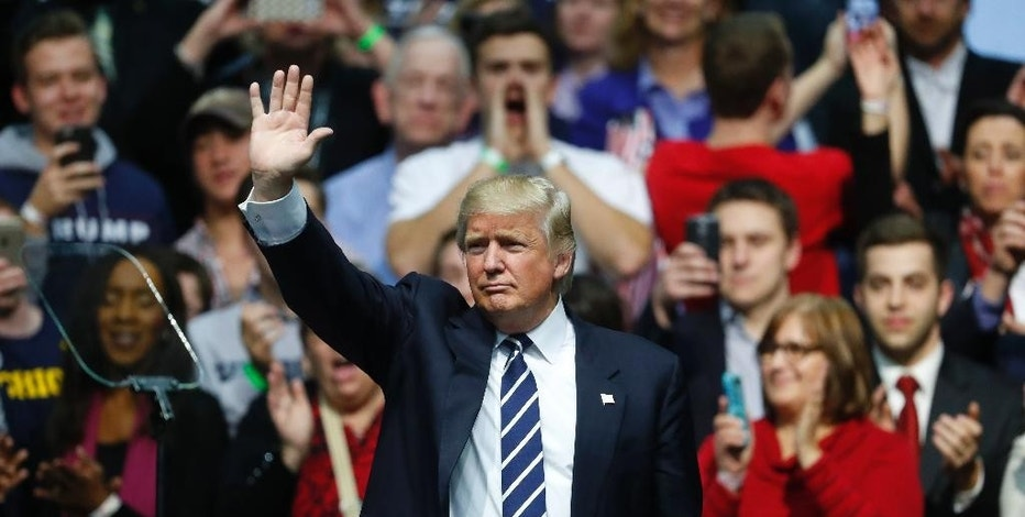 FILE - In this Friday, Dec. 9, 2016, file photo, President-elect Donald Trump waves to supporters during a rally in Grand Rapids, Mich. Trump's ambitious plans to revive American exports, keep jobs in the United States and encourage oil drilling face a home-grown threat: the surging U.S. dollar. Since the Nov. 8 election, the U.S. dollar has climbed to a 14-year high against the currencies of America's major trading partners. (AP Photo/Paul Sancya, File)