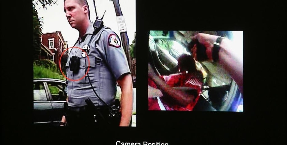 FILE - This Nov. 3, 2016 file photo shows a photograph of University of Cincinnati police officer Ray Tensing and his body camera footage which was  presented on the second day of witness testimony in the courtroom of Common Pleas Judge Megan Shanahan at the Hamilton County Courthouse, in Cincinnati. The Ohio Supreme Court has rejected a lawsuit brought by several news organizations arguing that video footage from police bodycams is a public record that should be released on request. The court on Tuesday, Dec. 20 unanimously denied the request since the video was released two days after the request. The bodycam footage involved the 2015 fatal shooting of a black motorist by Tensing, a white University of Cincinnati officer.(Cara Owsley/The Cincinnati Enquirer via AP, Pool, File)