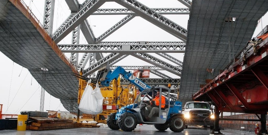 FILE - In this Nov. 15, 2016, file photo, a worker lifts materials as construction continues on the new roadway deck of the Bayonne Bridge in Bayonne, N.J. Even as they maneuver for a share of the $1 trillion in spending President-elect Donald Trump promised to rebuild America's roads, bridges and airports, lobbyists for transportation and utility industries are beginning to wonder whether Trump really meant what he said. From the day he formally entered the presidential race to the moment he declared victory, Trump pledged to rebuild the nation's aging and inadequate infrastructure.  (AP Photo/Mel Evans, File)