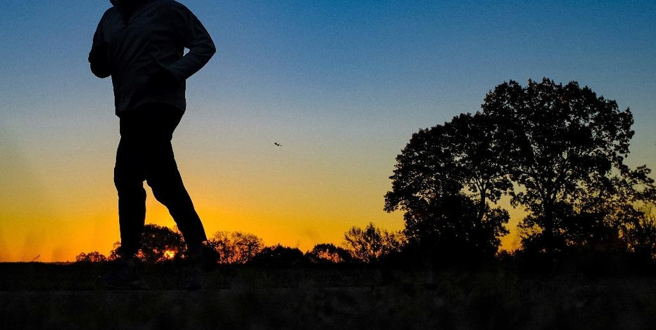 FILE - In this Tuesday, Nov. 22, 2016, file photo, a runner is silhouetted against the sunrise on his early morning workout near Arlington National Cemetery, across the Potomac River from the Nation's Capital, in Arlington, Va. Investors who are 70 1/2 or older should take their required minimum distributions from tax-deferred retirement accounts by the end of the year to avoid hefty penalties. Those who turned 70 1/2 in 2016 get an extension, but it's probably best not to wait. (AP Photo/J. David Ake, File)