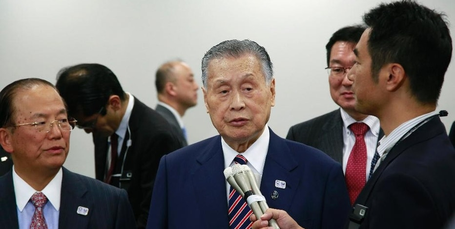 Tokyo Olympics Organizing Committee President Yoshiro Mori, center, answers a reporter's question after the four-party working group meeting in Tokyo, Wednesday, Dec. 21, 2016.  Organizers of the Tokyo Olympics estimate the total cost to host the 2020 Games will be between 1.6 and 1.8 trillion yen ($13-$15 billion). The official cost estimate announced Wednesday was slightly below the promised 2 trillion ($17 billion) cap.(AP Photo/Shizuo Kambayashi)