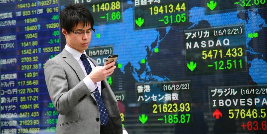 A man uses a mobile phone in front of an electronic stock indicator of a securities firm in Tokyo, Thursday, Dec. 22, 2016. Shares were meandering in thin trading Thursday in Asia, as investors wound down ahead of the holidays. (AP Photo/Shizuo Kambayashi)