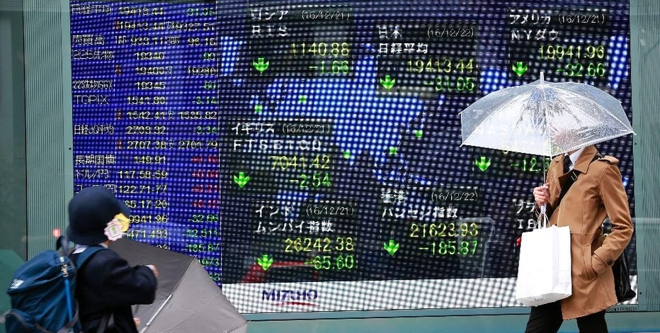A man looks at an electronic stock indicator of a securities firm in Tokyo, Thursday, Dec. 22, 2016. Shares were meandering in thin trading Thursday in Asia, as investors wound down ahead of the holidays. (AP Photo/Shizuo Kambayashi)
