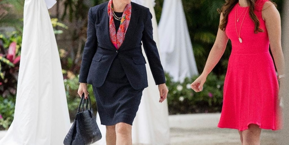 Lockheed Martin CEO Marillyn Hewson, left, accompanied by Madeleine Westerhout of the Republican National Committee, right, arrives at Mar-a-Lago, in Palm Beach, Fla., Wednesday, Dec. 21, 2016. (AP Photo/Andrew Harnik)