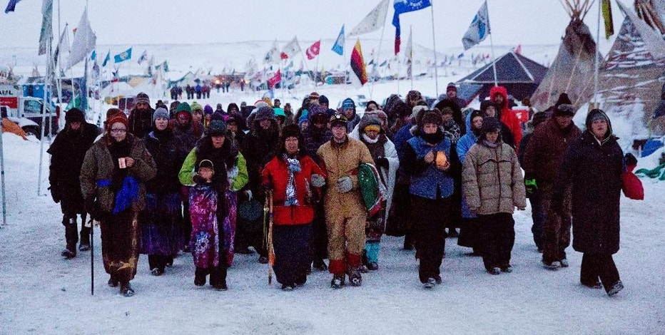 FILE - In this Thursday, Dec. 1, 2016, file photo, Beatrice Menase Kwe Jackson, center, walks with Daniel Emory, both of the Ojibwe Native American tribe as they lead a procession to the Cannonball river for a traditional water ceremony at the Oceti Sakowin camp where people have gathered to protest the Dakota Access oil pipeline in Cannon Ball, N.D. Some Native Americans worry the transition to a Donald Trump administration signals an end to eight years of sweeping Indian Country policy reforms. Trump rarely acknowledged Native Americans during his campaign. And he hasn't publicly outlined since the election how he would improve or manage the United States' longstanding relationships with tribes. (AP Photo/David Goldman, File)