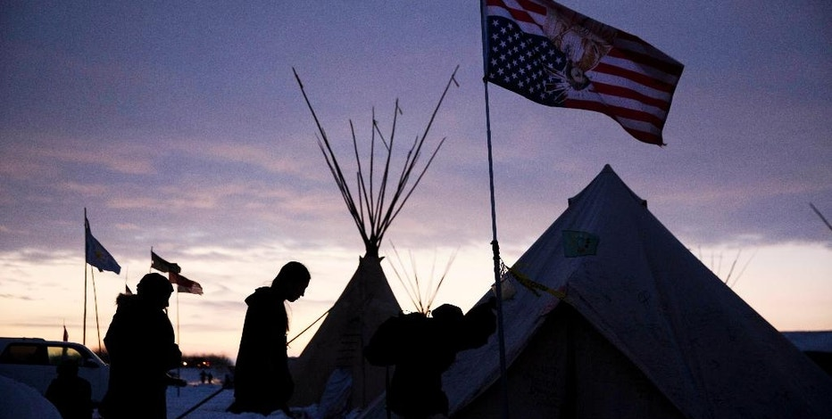FILE - In this Dec. 2, 2016, file photo, travelers arrive at the Oceti Sakowin camp where people have gathered to protest the Dakota Access oil pipeline as they walk into a tent next to an upside-down american flag in Cannon Ball, N.D. Some Native Americans worry the transition to a Donald Trump administration signals an end to eight years of sweeping Indian Country policy reforms. But Trump's Native American supporters said they're hopeful he will cut through some of the government red tape that they believe has stifled economic progress on reservations. (AP Photo/David Goldman, File)