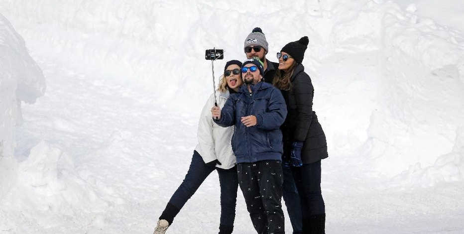 In this photo taken Friday, Dec. 16, 2016, a group of people huddle together to take a selfie photo on a cell phone at the Paradise area at Mount Rainier National Park, Wash. Spotty or no cellular service has been the norm at the nation's fifth oldest park south of Seattle, but that could change soon. Some say cell service would improve safety and provide a convenience for visitors. Others don't want it, saying the proliferation of phones will distract from the natural beauty of the surroundings. (AP Photo/Elaine Thompson)
