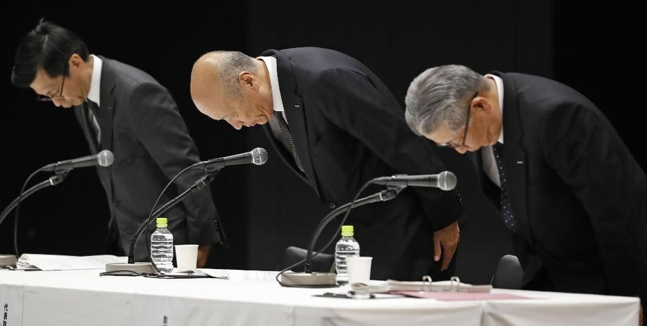President of the top Japanese advertising company Dentsu Inc. Tadashi Ishii, center, bows with other senior executives during a press conference at the company's headquarters in Tokyo, Wednesday, Dec. 28, 2016. President Ishii will step down to take responsibility for the suicide of a worker who had clocked massive overtime. (Kyodo News via AP)
