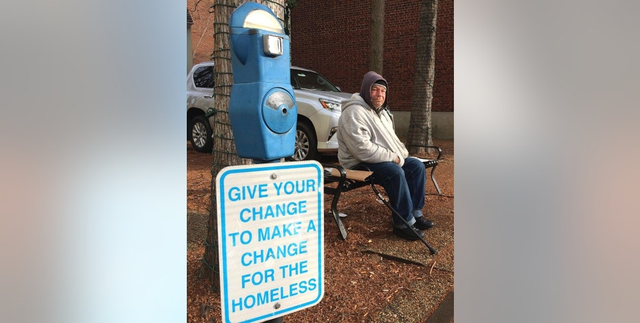 In this Tuesday, Dec. 27, 2016 photo, Joe Drury, who said he is homeless, sits near a parking-style meter in Annapolis, Md., used to collect loose change from those who might otherwise give money to those begging on the street. Drury said the meters may help charities, but they do nothing for him. The first of the meters designed to help the homeless went up in Denver in 2007 and dozens of other cities have followed suit. (AP Photo/Pat Eaton-Robb)