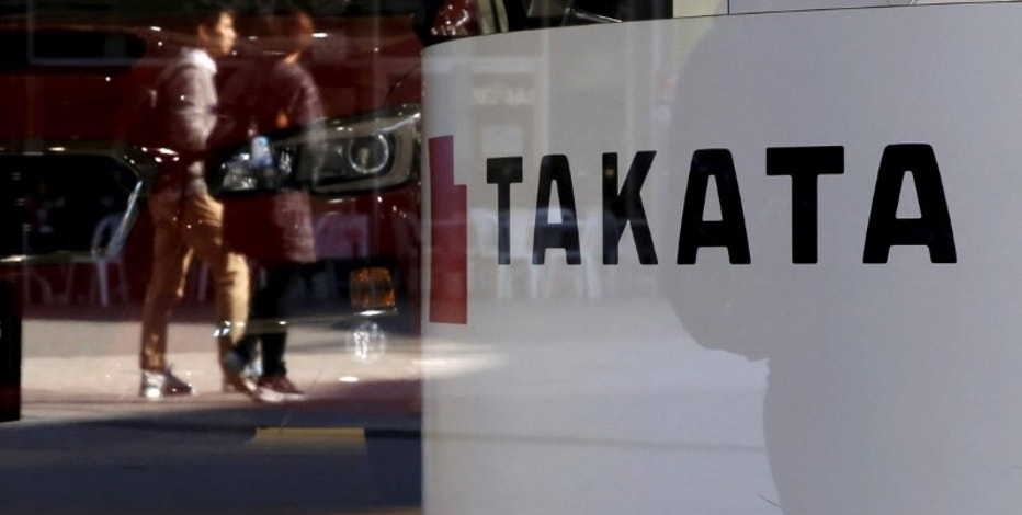 A logo of Takata Corp is seen with its display as people are reflected in a window at a showroom for vehicles in Tokyo, November 6, 2015. REUTERS/Toru Hanai/File Photo