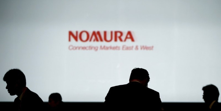 Investors stand in front of a screen showing the logo of Nomura Holdings in Tokyo, Japan, in this December 1, 2015 file photo. REUTERS/Toru Hanai/Files