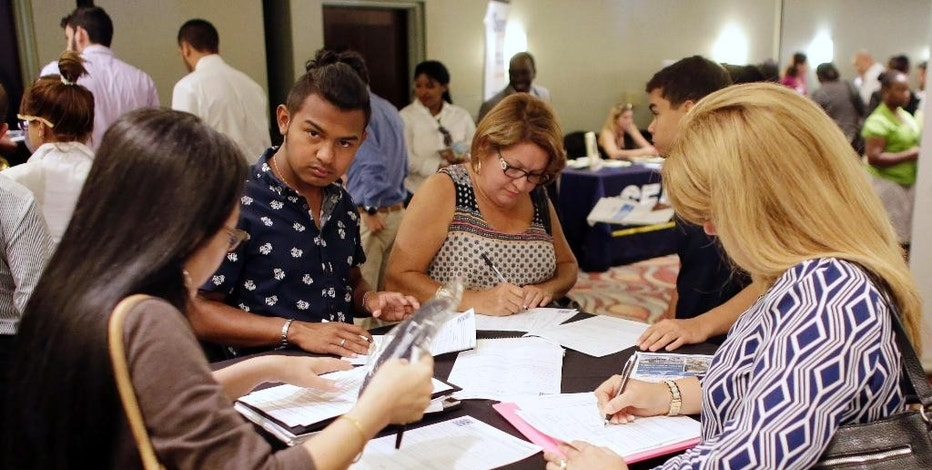 FILE - In this July 19, 2016, file photo, people fill out job applications at a job fair in Miami Lakes, Fla. On Thursday, Dec. 29, 2016, the Labor Department reported that fewer Americans applied for unemployment benefits the week before. (AP Photo/Lynne Sladky, File)