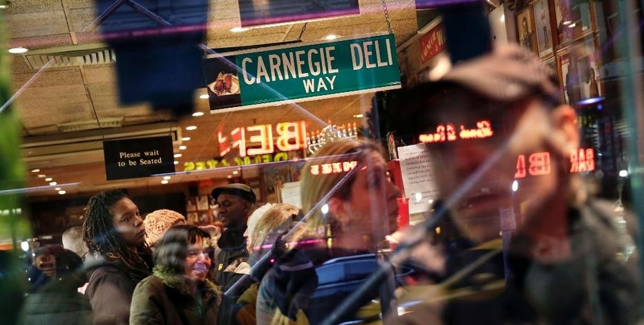 People wait in line, both inside and outside, to eat at the Carnegie Delicatessen in New York, Thursday, Dec. 29, 2016. After 79 years of serving up heaps of cured meat, the Carnegie slices its last ridiculously oversized sandwich Friday. (AP Photo/Seth Wenig)