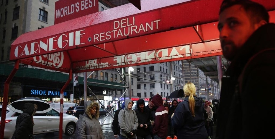 People wait in line to eat at the Carnegie Delicatessen in New York, Thursday, Dec. 29, 2016. After 79 years of serving up heaps of cured meat, the Carnegie slices its last ridiculously oversized sandwich Friday. Days before it shuts its doors, the line stretched down the block outside the Manhattan deli as hungry patrons waited to chow down on its famous $20 pastrami sandwich. (AP Photo/Seth Wenig)