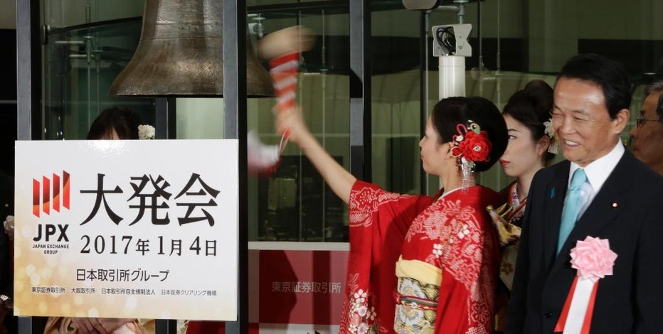 A Kimono-clad employee of the Tokyo Stock Exchange tolls a bell as Finance Minister Taro Aso, right, smiles after a ceremony marking the start of this year's trading in Tokyo Wednesday, Jan. 4, 2017. (AP Photo/Eugene Hoshiko)