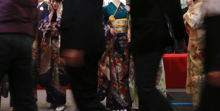 Kimono-clad employees of the Tokyo Stock Exchange and models see guests off after a ceremony marking the start of this year's trading in Tokyo Wednesday, Jan. 4, 2017. (AP Photo/Eugene Hoshiko)
