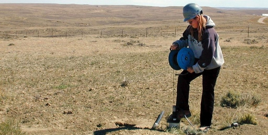 FILE - In this Sept. 14, 2004, file photo, Smith Ranch-Highland employee, April Frausto, samples water for contamination, at a monitoring well on the perimeter of the uranium mining zone 30 miles north of Douglas, Wyo. The Environmental Protection Agency is reconsidering plans to require groundwater at former uranium mines to be restored to conditions similar to those that existed before mining began. (AP Photo/Robert Black, File)
