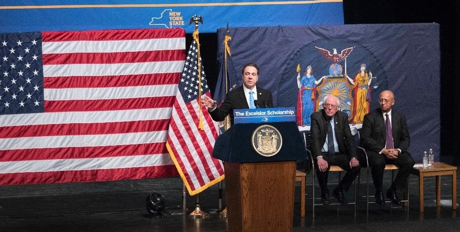 New York Gov. Andrew Cuomo, left, is joined by Vermont Sen. Bernie Sanders, center, and Chairperson of the Board of Trustees of The City University of New York William C. Thompson, as he speaks during an event at LaGuardia Community College, Tuesday, Jan. 3, 2017, in New York. Gov. Cuomo announced a proposal for free tuition at state colleges to hundreds of thousands of low- and middle income residents. Under the governor's plan, which requires legislative approval, any college student accepted to a New York public university or two-year community college is eligible, provided their family earns less than $125,000. (AP Photo/Mary Altaffer)