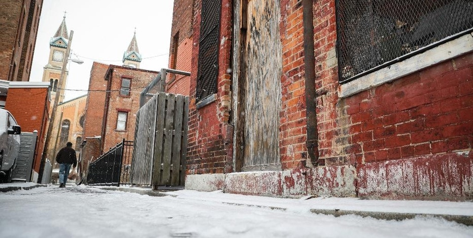 Pedestrians pass boarded up buildings in downtown Cincinnati, Thursday, Jan. 5, 2017. Boarded-up property will no longer be synonymous with blight in Ohio. With the Gov. John Kasich's signature Wednesday, the state has become the first to outlaw the use of plywood on abandoned and vacant properties. (AP Photo/John Minchillo)