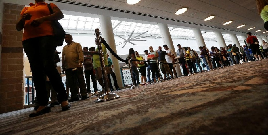 FILE - In this Sept. 3, 2014 file photo, people wait in line to sign up for unemployment in Atlantic City, N.J. The proportion of men in their prime working years who have a job has been steadily declining _ and holding back the United States' growth potential. The full brunt of this 60-year decline became apparent during the 2016 election. Trump won the electoral college in large part by calling for more jobs at steel mills, auto plants and coal mines, the types of work that had once employed legions of men who lacked a college education.  (AP Photo/Mel Evans, File)