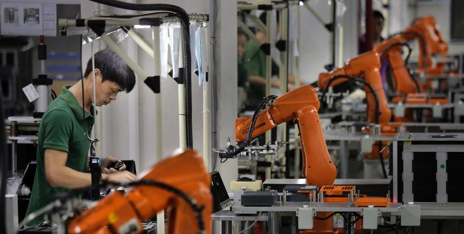 FILE - In this Aug. 21, 2015 photo, a man works amid orange robot arms at Rapoo Technology factory in southern Chinese industrial boomtown of Shenzhen.  The job market has changed under President Barack Obama's 8 years.  Manufacturing, office admin work has fallen, due to globalization and automation.   (AP Photo/Vincent Yu)