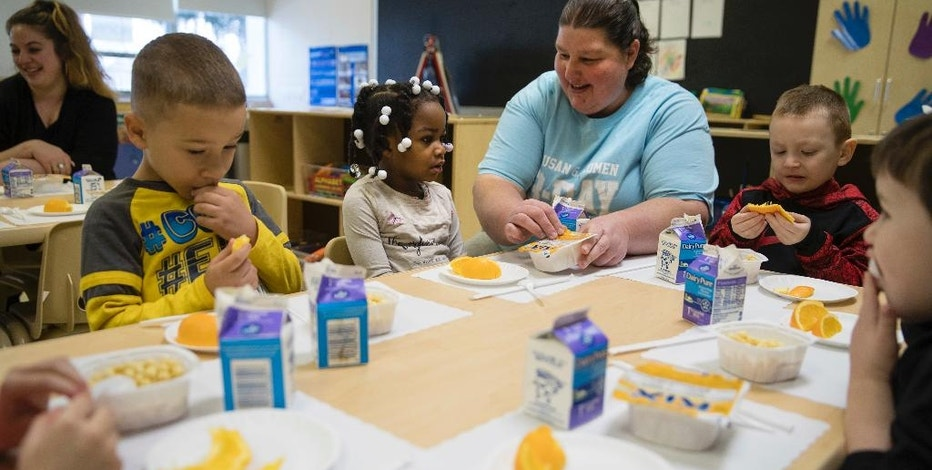 Teacher Patty Cronin helps three-year-old Makayla Grant open her package of cereal during preschool in Philadelphia, Friday, Jan. 6, 2017. Thousands of Philadelphia toddlers are starting 2017 in a city pre-kindergarten program, launched this week alongside a new sugary beverage tax created to fund it.   (AP Photo/Matt Rourke)