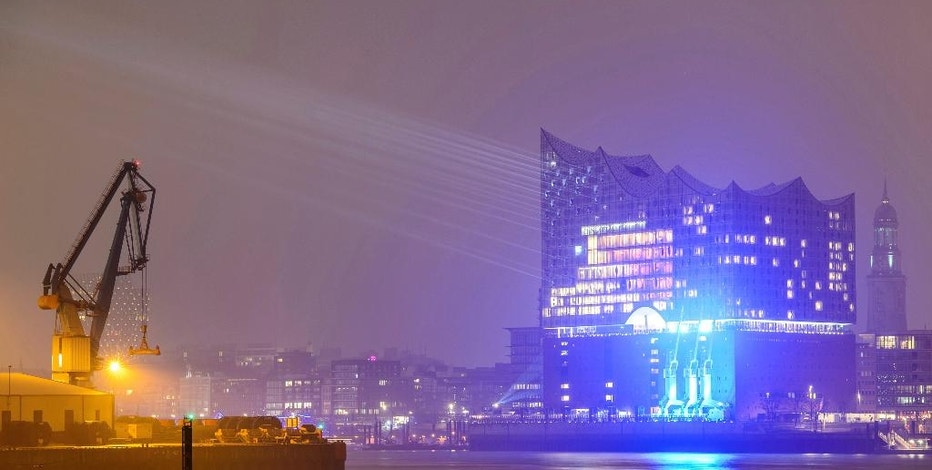 In this Jan. 8, 2017 photo the building of the Elbphilharmonie, the philharmonic orchestra concert hall, is illuminated by a light show test at the harbour in Hamburg, Germany. The concert hall will be inaugurated on Jan. 11, 2017. (Daniel Reinhardt/dpa via AP)