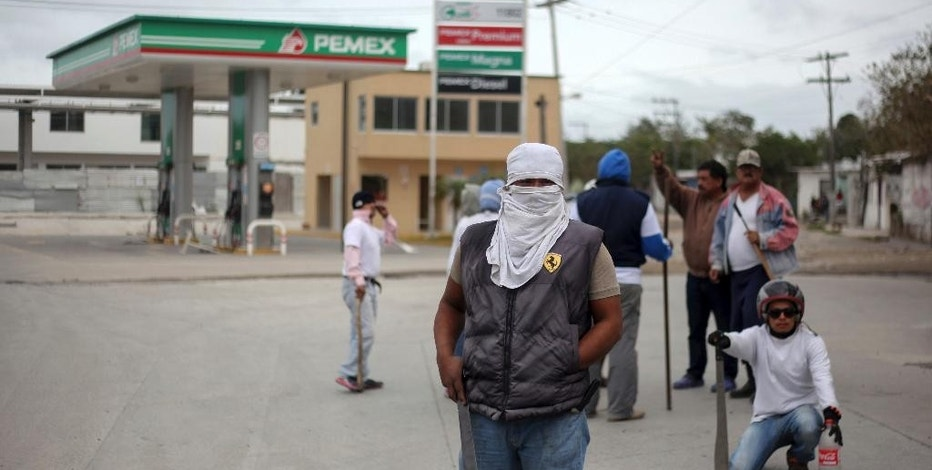 Masked men stand guard in front of a gas station in Veracruz, Mexico, Saturday, Jan. 7, 2017. As looting as largely subsided in Mexico, following a 20 percent hike in gasoline prices, neighborhoods in affected áreas have taken to guarding themselves from potential looters. (AP Photo/Felix Marquez)