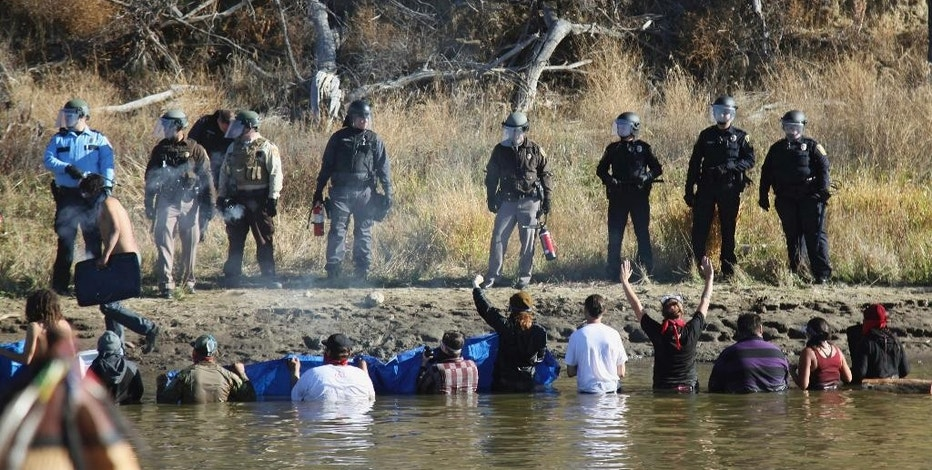 FILE - In this Nov. 2, 2016 file photo, protesters demonstrating against the expansion of the Dakota Access Pipeline wade in cold creek waters confronting local police near Cannon Ball, N.D. The cost of policing the Dakota Access pipeline protests in North Dakota is at least $22 million — more than $5 million more than the state set aside last year. Protest-related funding decisions will be made by state lawmakers during the 2017 session. Leaders of the House and Senate appropriation committees say more funding will be approved, though the amount and method isn't known. (AP Photo/John L. Mone, File)