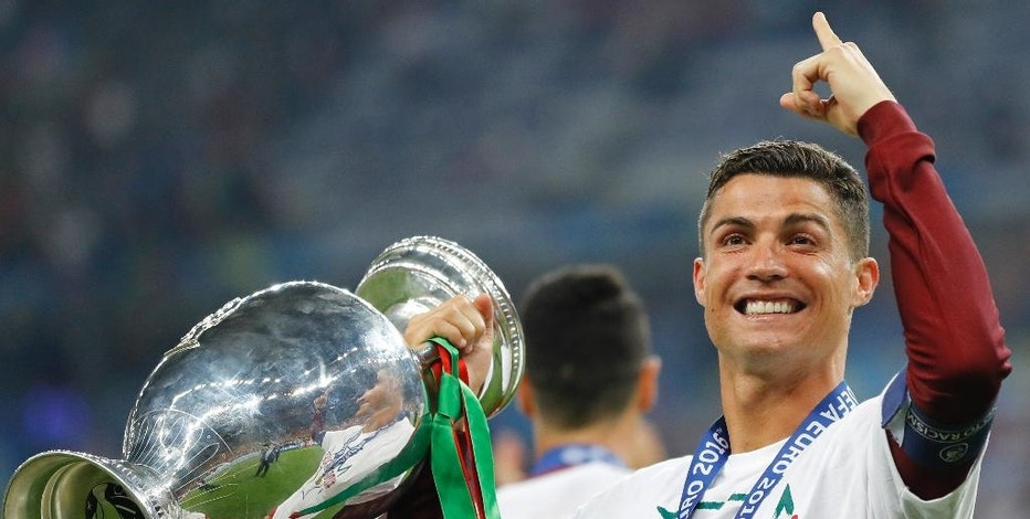 FILE - In this Sunday, July 10, 2016 file photo, Portugal's Cristiano Ronaldo celebrates with the trophy at the end of the Euro 2016 final soccer match between Portugal and France at the Stade de France in Saint-Denis, north of Paris. Cristiano Ronaldo is one of the nominees for FIFA's world's best player award on Monday Jan. 9, 2017. (AP Photo/Frank Augstein, File)