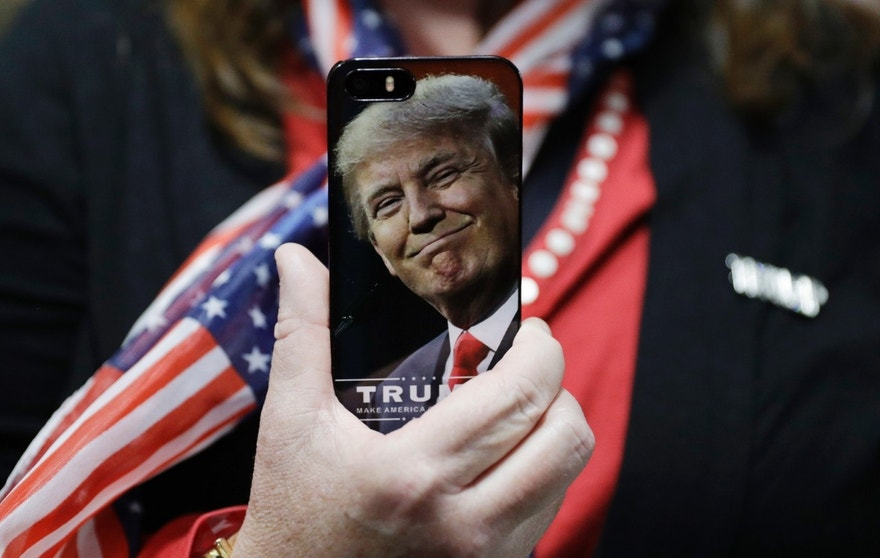 FILE - In this Thursday, Sept. 29, 2016, file photo, a woman holds up her cell phone before a rally with then presidential candidate Donald Trump in Bedford, N.H. President-elect Trump tweeted Tuesday that North Korea won't develop a nuclear weapon capable of reaching parts of the United States, but it's possible it already has. After five atomic test explosions and a rising number of ballistic missile test launches, many experts believe that North Korea can arm short- and mid-range missiles with warheads that put Guam at risk. (AP Photo/John Locher, File)
