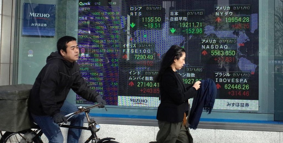 People pass by an electronic stock board showing Japan's Nikkei stock index at a securities firm in Tokyo, Thursday, Jan. 12, 2017. Asian shares were mixed Thursday following President-elect Donald Trump's press conference. Trump offered scant details on policies, disappointing investors hoping for a clearer sense of his plans for trade and economic stimulus. (AP Photo/Shuji Kajiyama)