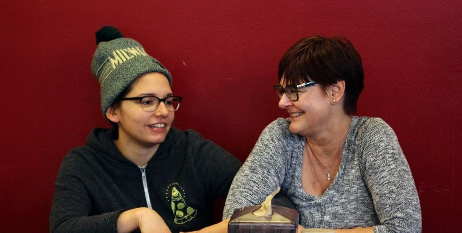 In this Jan. 9, 2017, photo, Andrea Ledesma, left, talks with her mother, Cheryl Romanowski, at Classic Slice pizza restaurant, where Ledesma works, in Milwaukee. Ledesma, 28, says her parents owned a house and were raising kids by her age. Not so for her, even though she has a college degree. With a median household income of $40,581, millennials earn 20 percent less than boomers did at the same stage of life, despite being better educated, according to a new analysis of Federal Reserve data by the advocacy group Young Invincibles. (AP Photo/Carrie Antlfinger)